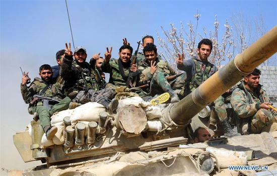 Syrian soldiers flash the victory sign on their tank in the town of Aftaris in Damascus' Eastern Ghouta countryside, Syria, on March 12, 2018. Syrian army captured on Monday the town of Aftaris in Eastern Ghouta, the latest town to be retaken by the army during the wide-scale offensive in that area, state news agency SANA said. (Xinhua/Ammar Safarjalani)