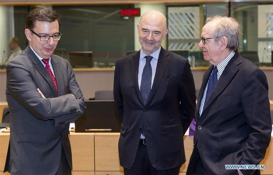 Spanish Economy, Industry and Competitiveness Minister Roman Escolano (L), European Commissioner for Economic and Financial Affairs, Taxation and Customs Pierre Moscovici (C) and Italian Finance Minister Pier Carlo Padoan talk prior to a meeting of Eurogroup finance ministers in Brussels, Belgium, March 12, 2018. Eurogroup President Mario Centeno said Monday that the eurozone bailout fund is expected to disburse the next tranche, worth 5.7 billion euros (7.03 billion U.S. dollars), to Greece in the second half of March. (Xinhua/Thierry Monass)