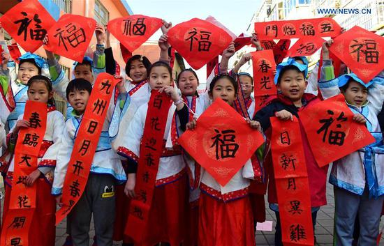 Pupils of Chinese calligraphy hobby group present Spring Festival couplets written by themselves at a community in Cangzhou, north China's Hebei Province, Feb. 5, 2018. (Xinhua/Fu Xinchun)