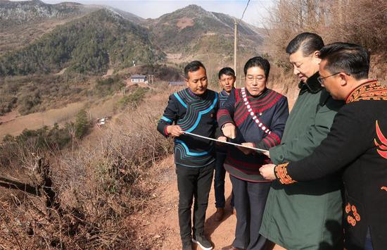 Chinese President Xi Jinping, also general secretary of the Communist Party of China Central Committee, listens to the planning of relocation site for residents from poor areas as he visits Sanhe Village of Sanchahe Township in Zhaojue County of Liangshan Yi Autonomous Prefecture, southwest China's Sichuan Province, Feb. 11, 2018. Xi made an inspection tour in Sichuan Province on Feb. 11. (Xinhua/Ju Peng)