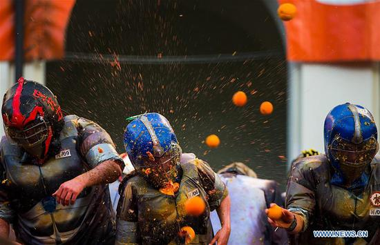 Members of a team fight with oranges during an annual historical carnival
