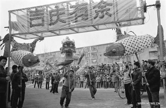 File photo taken in February 1985 shows villagers performing festive lanterns in Duandian Village of Jinan City, east China's Shandong Province. In Chinese villages, people have their distinctive ways to celebrate the Spring Festival. Simple but joyful, the celebrations bring them gratification and happiness. Spring festival, or better known as Chinese Lunar New year, is the most important festival for all Chinese, which has a history of more than 4,000 years. It is an occasion for home returning, New Year goods preparing, celebrating, and foremost, family reunion. (Xinhua/Li Jin)