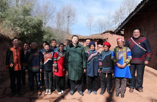 Chinese President Xi Jinping, also general secretary of the Communist Party of China Central Committee, poses for a group photo with villagers at the home of an impoverished family as he visits Sanhe Village of Sanchahe Township in Zhaojue County of Liangshan Yi Autonomous Prefecture, southwest China's Sichuan Province, Feb. 11, 2018. Xi made an inspection tour in Sichuan Province on Feb. 11. (Xinhua/Xie Huanchi)