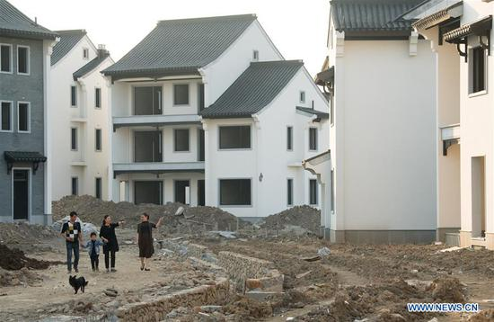 Villagers walk at a new residential area under construction in Dazhuyuan Village of Anji County, east China's Zhejiang Province, Nov. 2, 2017. China's annual political sessions of the National People's Congress (NPC) and the National Committee of the Chinese People's Political Consultative Conference (CPPCC) are scheduled to convene in March, 2018. During the two sessions, development agendas will be reviewed and discussed, and key policies will be adopted. According to the 13th five-year plan for economic and social development of China covering the period 2016 to 2020, coordination has been emphasized as an integral quality of sustained and healthy development, which underlines advancing coordinated development between rural and urban areas, between different regions, and between economic and social development. (Xinhua/Weng Xinyang)