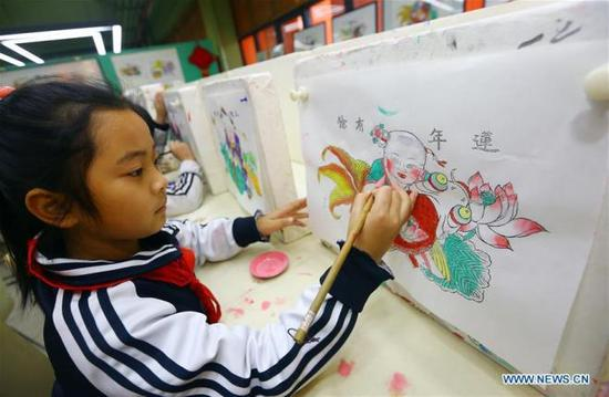 A girl learns to paint new year picture at Puyu School in north China's Tianjin Municipality, Jan. 3, 2018. Intangible cultural heritage lessons, such as Yangliuqing new year painting, paper cutting and traditional drum performance, were introduced into the school. (Xinhua/Liu Dongyue)