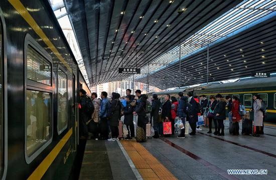 Passengers line up to board a train at the Beijing West Railway Station in Beijing, capital of China, Feb. 12, 2018. The number of passenger trips around China hit 108.363 million from Feb. 1 to Feb. 12 this year. The Spring Festival travel rush began on Feb. 1 and will last until March 12. The China National Tourism Administration said that 385 million trips, mostly domestic, are expected to be made during the Spring Festival 2018, up 12 percent year on year. (Xinhua/Zeng Tao)
