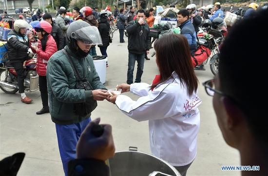 A volunteer offers free rice soup to a migrant worker at Xiaoxiang service station in Zhaoqing, south China's Guangdong Province, Feb. 7, 2018. Many migrant workers in China chose to go home by motorcycle for a family reunion in the Spring Festival, or Chinese traditional lunar New Year. (Xinhua/Liang Xu)