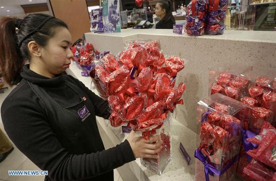 A staff member arranges a flower-shaped chocolate bouquet at a candy shop in Vancouver, Canada, on Feb. 13, 2018. Chocolate retailers in Vancouver prepared a variety of Valentine-themed products for the upcoming Valentine's Day. (Xinhua/Liang Sen)