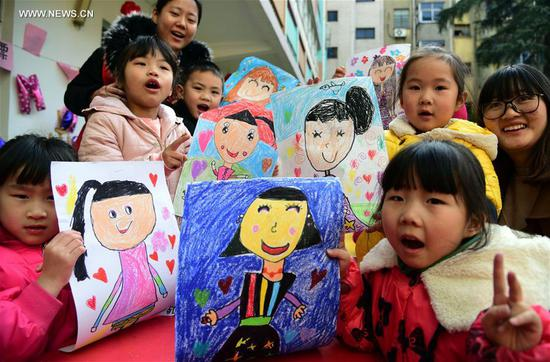 Children show their drawings depicting their mothers during an activity ahead of the International Women's Day at Chaoyanglou kindergarten in Zhenjiang City, east China's Jiangsu Province, March 6, 2018. (Xinhua/Shi Yucheng)