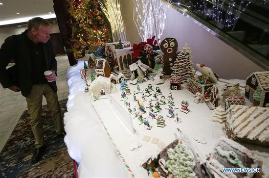 A visitor admires gingerbread houses displayed at the 27th annual Gingerbread Lane competition in Vancouver, Canada, Dec. 4, 2017. A total of 33 local amateur and professional cakemakers participated in the event and showed their works to visitors. (Xinhua/Liang Sen)
