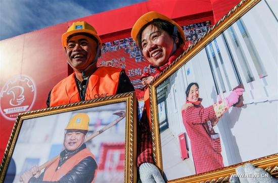 Construction worker Huang Chunping (L) and cleaner Zeng Feng display their portrait photos in Beijing, capital of China, Jan. 9, 2018. A team consisted of press photographers and photographic enthusiasts volunteered to make portraits for workers on their jobs from construction and other industries. More than 1,000 workers received their photos on Tuesday. (Xinhua/Li Xin)