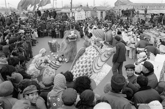 File photo taken in February 1985 shows a festive lantern troupe performing before the Spring Festival in Luokou Village of Jinan City, east China's Shandong Province. In Chinese villages, people have their distinctive ways to celebrate the Spring Festival. Simple but joyful, the celebrations bring them gratification and happiness. Spring festival, or better known as Chinese Lunar New year, is the most important festival for all Chinese, which has a history of more than 4,000 years. It is an occasion for home returning, New Year goods preparing, celebrating, and foremost, family reunion. (Xinhua/Shi Panqi)