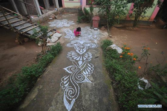 "A girl paints ""Alpona"" on the courtyards of their houses in Agartala, capital of the India's northeastern state Tripura, Jan. 13, 2018. Makar Sankranti is one of the most auspicious occasions for the Hindus which is celebrated in almost all parts of India and Nepal. (Xinhua/Saha)"