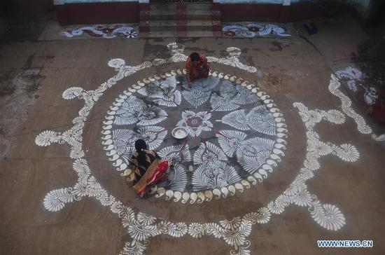 "Woman paint ""Alpona"" on the courtyards of their houses in Agartala, capital of the India's northeastern state Tripura, Jan. 13, 2018. Makar Sankranti is one of the most auspicious occasions for the Hindus which is celebrated in almost all parts of India and Nepal. (Xinhua/Saha)"