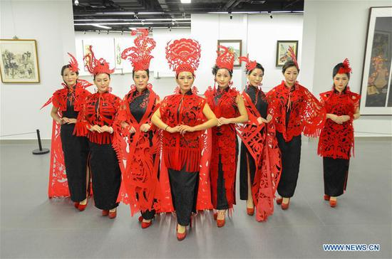 Photo taken on Feb. 10, 2018 shows cheongsam hobbyists dressed in cheongsam decorated with paper cuttings designed by Liang Ying in Liaocheng, east China's Shandong Province. Liang Ying, provincial-level inheritor of traditional Chinese paper cutting, which is one of the intangible cultural heritages, designs paper cutting ornaments for the cheongsam, or qipao in Mandarin Chinese, to greet the Chinese lunar New Year. (Xinhua/Xu Wenhao)