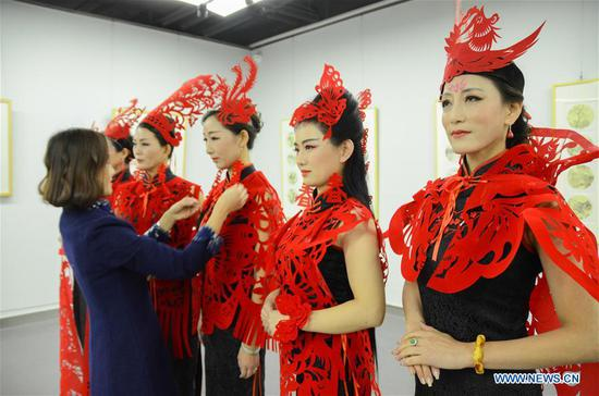 Liang Ying makes up for the cheongsam hobbyists in Liaocheng, east China's Shandong Province, Feb. 10, 2018. Liang Ying, provincial-level inheritor of traditional Chinese paper cutting, which is one of the intangible cultural heritages, designs paper cutting ornaments for the cheongsam, or qipao in Mandarin Chinese, to greet the Chinese lunar New Year. (Xinhua/Xu Wenhao)