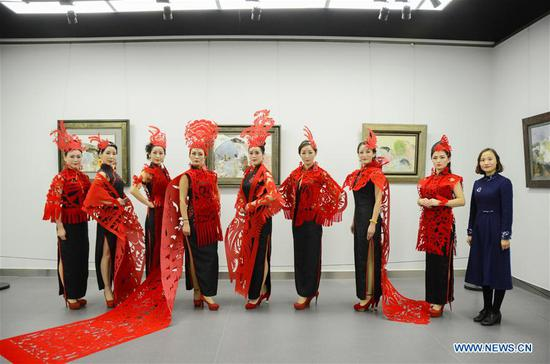 Photo taken on Feb. 10, 2018 shows cheongsam hobbyists dressed in cheongsam decorated with paper cuttings, with the designer Liang Ying (1st R) in Liaocheng, east China's Shandong Province. Liang Ying, provincial-level inheritor of traditional Chinese paper cutting, which is one of the intangible cultural heritages, designs paper cutting ornaments for the cheongsam, or qipao in Mandarin Chinese, to greet the Chinese lunar New Year. (Xinhua/Xu Wenhao)