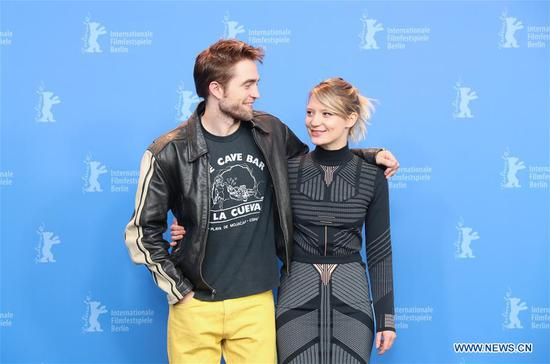 Actor Robert Pattinson (L) and actress Mia Wasikowska pose for photos during the photocall of film
