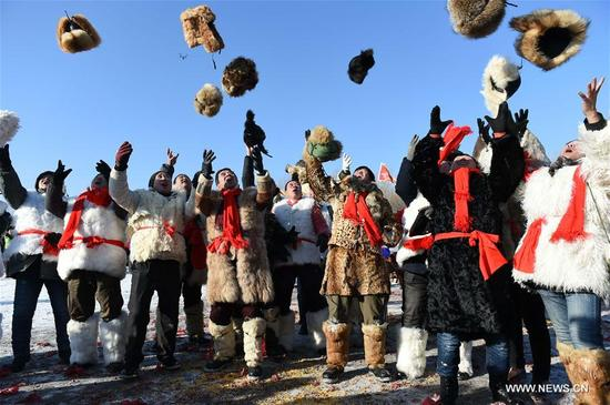 People throw their hats during a folk ceremony marking the beginning of ice collecting season in Harbin, capital of northeast China's Heilongjiang Province, Dec. 3, 2017. For the coming month, workers will collect ice cube from the frozen Songhua River to prepare for the construction of the Ice and Snow World, where buildings of ice are illuminated by colorful lights. (Xinhua/Wang Jianwei)