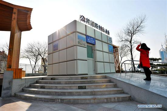 A visitor stands outside of a magic cube shaped public toilet in a scenic area in Qingdao, east China's Shandong Province, Nov. 30, 2017. The Chinese government launched its