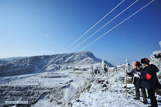 Staff members of Wuchuan Power Supply Bureau check supply lines in Wuchuan Gelao and Miao Autonomous County, southwest China's Guizhou Province, Jan. 9, 2018. According to China Southern Power Grid Guizhou Bureau, 256 on-line alert terminal devices are launched to make sure the stable operation of power supply, since they issued a blue alert for ice weather on Jan. 6. (Xinhua/Tao Liang)