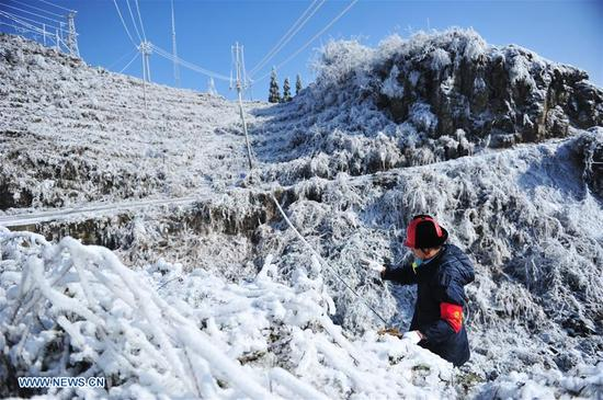 A staff member of Wuchuan Power Supply Bureau observes the thickness of ice covered on the supply line in Wuchuan Gelao and Miao Autonomous County, southwest China's Guizhou Province, Jan. 9, 2018. According to China Southern Power Grid Guizhou Bureau, 256 on-line alert terminal devices were launched to make sure the stable operation of power supply, since they issued a blue alert for ice weather on Jan. 6. (Xinhua/Tao Liang)