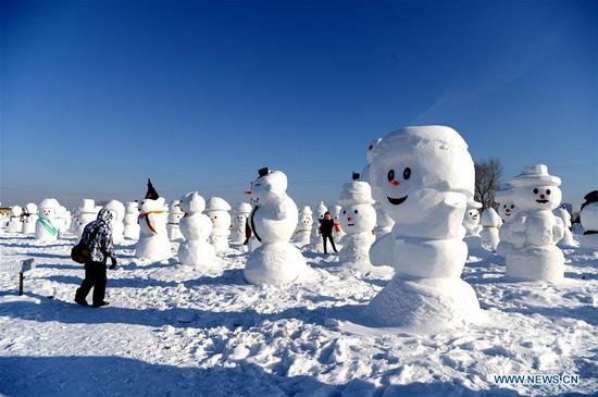 People watch snowman sculptures at an ice and snow park in Harbin, capital of northeast China's Heilongjiang Province, Jan. 11, 2018. Altogether 2,018 cute snowmen were displayed here to greet the year 2018. (Xinhua/Wang Kai)