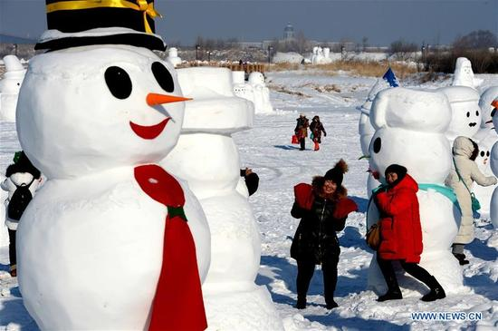People pose for photos with snowman sculptures at an ice and snow park in Harbin, capital of northeast China's Heilongjiang Province, Jan. 11, 2018. Altogether 2,018 cute snowmen were displayed here to greet the year 2018. (Xinhua/Wang Kai)