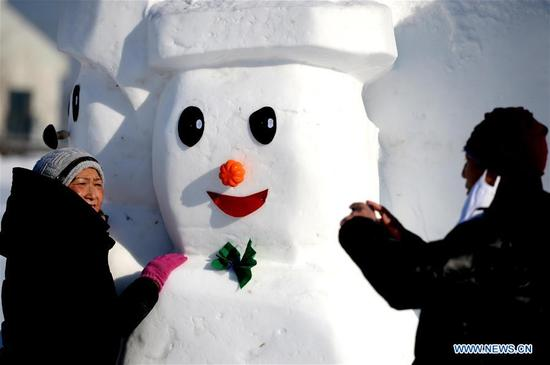 136People pose for photos with snowman sculptures at an ice and snow park in Harbin, capital of northeast China's Heilongjiang Province, Jan. 11, 2018. Altogether 2,018 cute snowmen were displayed here to greet the year 2018. (Xinhua/Wang Kai)