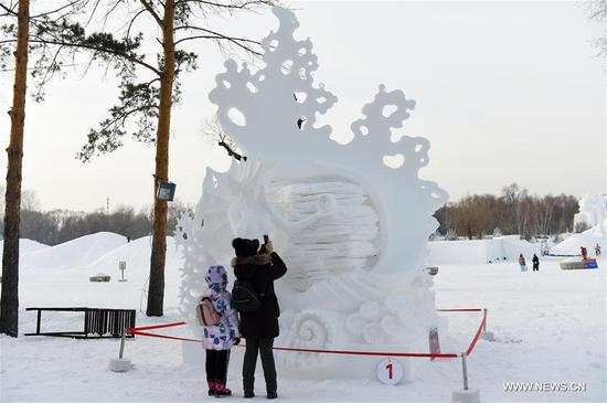 Tourists take photos of the work from Team Mingdao Sculpturing Harbin, The Spirit of the Sea which wins the second prize at the 23rd Harbin International Snow Sculpture Competition in Harbin, capital of northeast China's Heilongjiang Province, Jan. 13, 2018. The four-day competition concluded here on Saturday, with a total of 25 teams from home and abroad participating in the game. (Xinhua/Wang Jianwei)