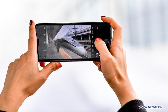 Zhang Yuliang takes photo of a high-speed train at the platform of the Chongqing North Railway Station in Chongqing, southwest China, Feb, 9, 2018. Zhang Yuliang, a 25-year-old girl from Chongqing, loves to record daily life by smart phone. She took photos of the trip from Chongqing North Railway Station to Dazu South Railway Station during the Spring Festival travel rush. (Xinhua/Liu Chan)