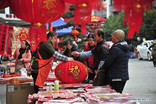 People buy red lanterns in Jiuzhou Ancient Town of Huangping County, southwest China's Guizhou Province, Feb. 13, 2018. Different cities around China were decorated to greet the upcoming Chinese Lunar New Year. (Xinhua/Wang Yonglong)