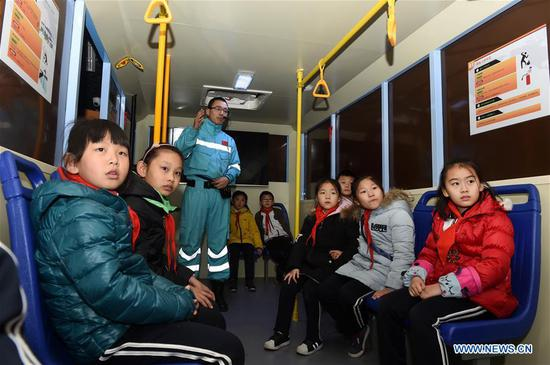 Children attend a lecture at a home safety training center in Qingdao, east China's Shandong Province, March 7, 2018. The Qingdao Municipal Women's Federation organized a home safety workshop on Wednesday, allowing participants to learn home safety knowledge and skills via on-the-spot training sessions. (Xinhua/Li Ziheng)