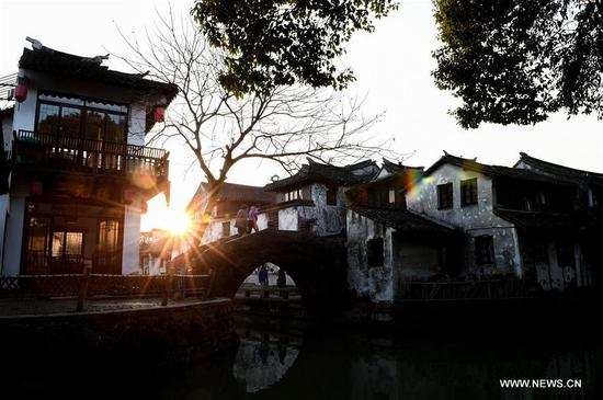 Tourists walk on a bridge in the ancient town of Zhouzhuang in Suzhou City, east China's Jiangsu Province, March 9, 2018. As temperature rises, the water town of Zhouzhuang becomes hot tourist destination. (Xinhua/Li Bo)
