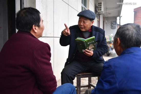 Li Chunru (C) talks about the protection of migratory birds with local residents near Poyang Lake nature reserve, east China's Jiangxi Province, Nov. 28, 2017. Poyang is a seasonal destination for over a million birds every year. Doctor Li Chunru has been voluntarily taken care of migratory birds at Poyang Lake nature reserve for more than 30 years, bringing over 50,000 wounded wild birds out of danger. (Xinhua/Hu Chenhuan)