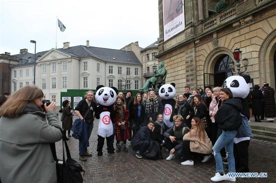 People pose with panda mascots outside the Royal Theater in Copenhagen, Denmark, Dec. 5, 2017. The 2017 China-Denmark Tourism Year wrapped up with a gala closing ceremony in the Danish capital city of Copenhagen on Tuesday. (Xinhua/Shi Shouhe)