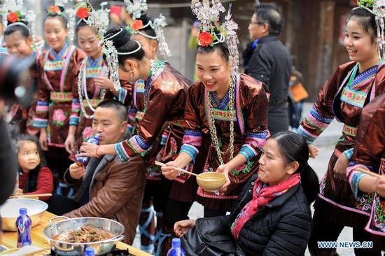 rongjiang girls Brightly costumed girls sing before a feast in zhongcheng township, rongjiang county of qiandongnan miao and dong autonomous prefecture, southwest china's guizhou province, dec 16, 2017 nearly 1,000 tourists enjoyed the niubie (a specially made cuisine) hotpot feast, on combined tables reaching a.