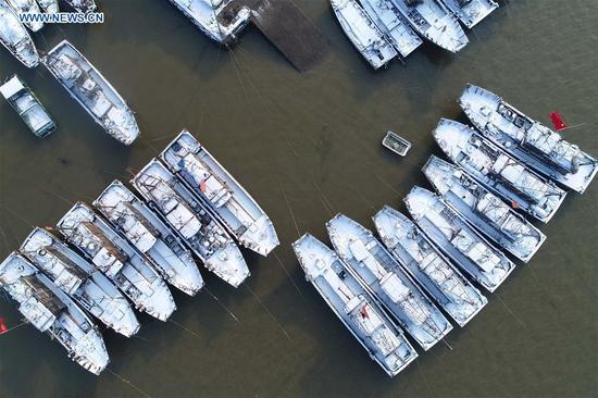 Fishboats are covered by snow in Liandao fishing village of Lianyungang City, east China's Jiangsu Province, Jan. 5, 2018, on the occasion of