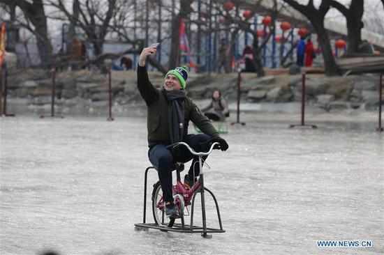 A tourist rides an ice bike in the ice rink at the Summer Palace in Beijing, capital of China, Jan. 7, 2018. During the weekend, many people came to the ice rink on Kunming Lake to relax or take exercise.(Xinhua/Liu Xianguo)