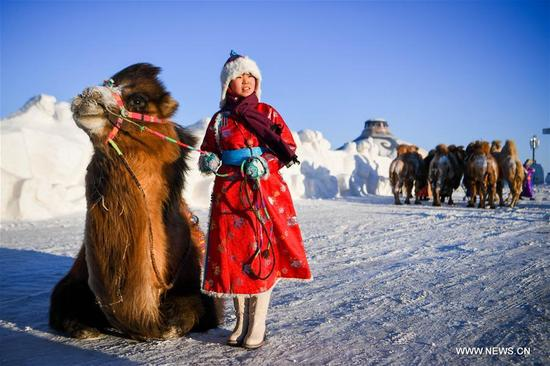 A girl of Mongolian ethnic group poses for photo with a camel in Sunite Right Banner, north China's Inner Mongolia Autonomous Region, Jan. 9, 2018. A camel fair, a local traditional festival including camel race and camel beauty contest, was held in the Banner on Tuesday. More than 200 camels took part in the fair. (Xinhua/Lian Zhen)