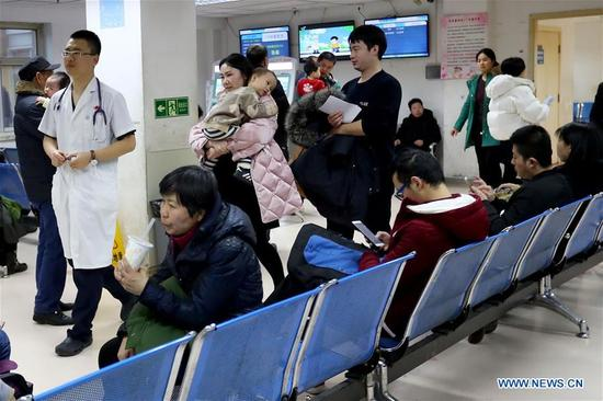 Children and their parents wait for treatment at Beijing Children's Hospital in Beijing, capital of China, Jan. 11, 2018. China's health authority has urged strengthened monitoring and treatment in face of the current influenza outbreak. The National Health and Family Planning Commission (NHFPC) in a circular asked medical organs at all levels to reserve enough antiviral medicines, and allocate medical resources and equipment such as respirators and monitors for timely treatment of severe cases. The commission also demanded close monitoring of the mutation of flu virus strains, and suggested schools have daily check-ups for students. (Xinhua/Zhang Yuwei)