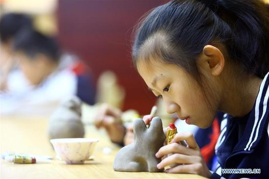 A girl learns to make clay sculpture at Puyu School in north China's Tianjin Municipality, Jan. 3, 2018. Intangible cultural heritage lessons, such as Yangliuqing new year painting, paper cutting and traditional drum performance, were introduced into the school. (Xinhua/Liu Dongyue)