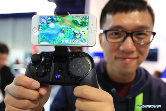 A staff member shows a Chinese Gamesir G5 gamepad at Consumer Electronics Show (CES) in Las Vegas, the United States, Jan. 10, 2018. (Xinhua/Li Ying)