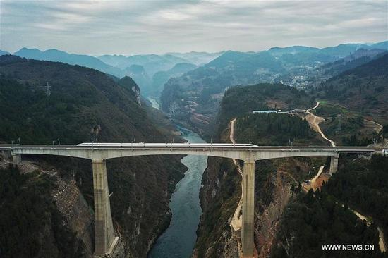 A bullet train runs on the Wujiang Bridge, southwest China's Guizhou Province, Jan. 13, 2018. A railway connecting two major cities in southwest China, Chongqing and Guiyang is under trial run. Designed for passenger trains running at a speed of 200 kilometers per hour, the railway will improve traffic between China's southwest and northwestern, eastern, southern areas. (Xinhua/Liu Xu)