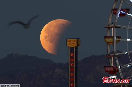 A lunar eclipse of a full blue moon is seen behind the Santa Monica Pier in Santa Monica, California, U.S., January 31, 2018. (Photo/Agencies)