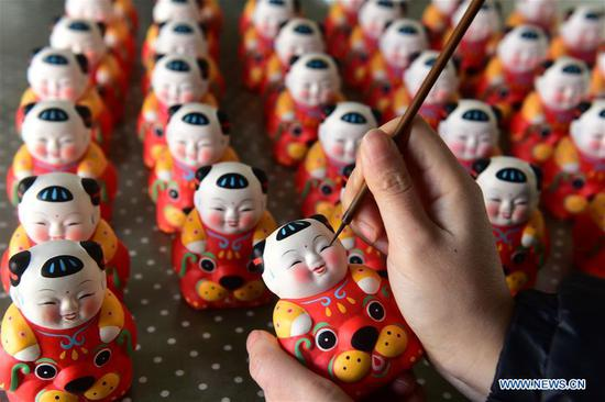A craftswoman colors Huishan clay figurines featuring the Chinese lunar New Year of Dog in Wuxi City, east China's Jiangsu Province, Feb. 2, 2018. (Xinhua/Huan Yueliang)