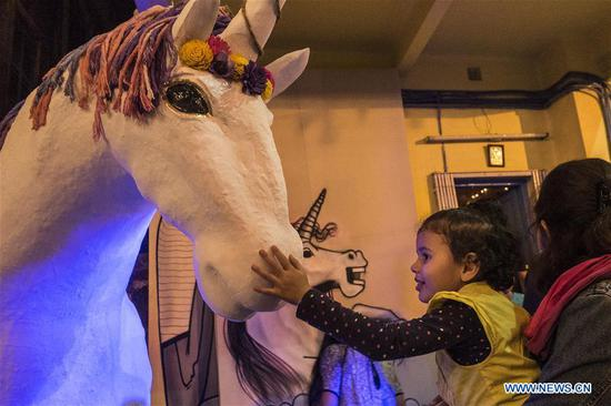 A child plays with a model of Unicorn at the Unicorn Street Art Festival in Kolkata, India Feb. 4, 2018. The festival theme was Unicorn, mythological animal resembling a horse with a single horn on its forehead. (Xinhua Photo/ Tumpa Mondal)