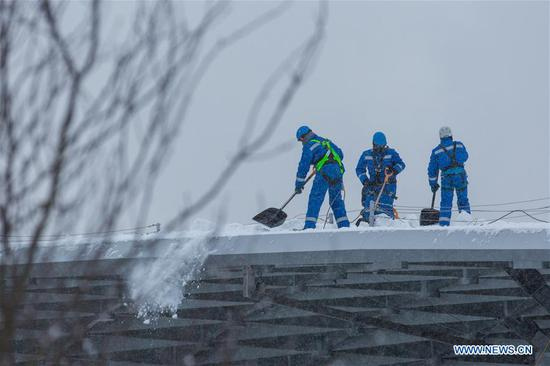 Workers remove snow on a roof in Moscow, Russia, on Feb. 5, 2018. Moscow experienced a record strong snowfall last week, which caused delays and cancellations of air flights and the death of at least one victim, officials said.