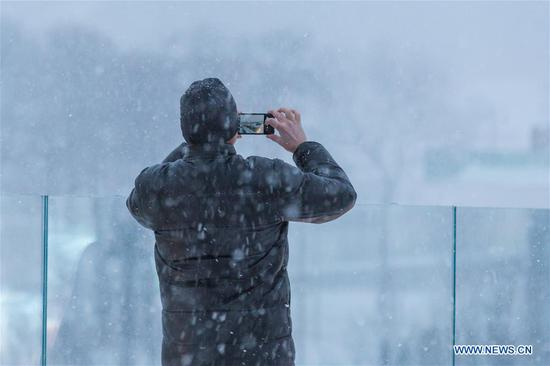 A man takes a picture at a park in Moscow, Russia, on Feb. 5, 2018. Moscow experienced a record strong snowfall last week, which caused delays and cancellations of air flights and the death of at least one victim, officials said.