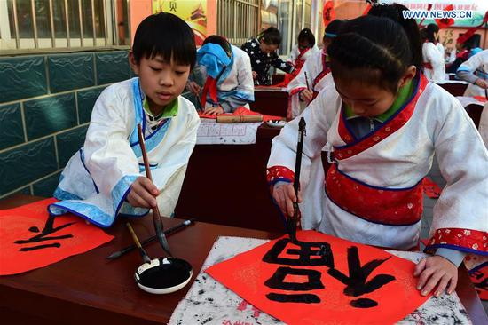 Pupils of Chinese calligraphy hobby group write couplets to celebrate the coming Spring Festival at a community in Cangzhou, north China's Hebei Province, Feb. 5, 2018. (Xinhua/Fu Xinchun)